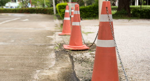 Mostphotos-22785550-close-up-bright-orange-traffic-cones-standing-in-a-row-on-asphalt.jpg